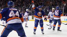 New York Islanders' Cal Clutterbuck, centre, increased the lopsided margin to 7-1 at 16:04 of the second period with his 11th goal of the season. (Bruce Bennett/Getty Images)
