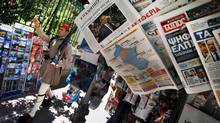 A presidential guard marches by a newspaper stand featuring news about Greece's election results in Athens on Monday, June 18. (PASCAL ROSSIGNOL/REUTERS)