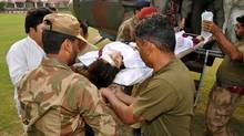 Pakistani soldiers carry an injured Malala Yousafzai on Tuesday after the 14-year-old schoolgirl was wounded in a gun attack. (ISPR/XINHUA/NEWSCOM)