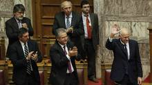 Lawmakers applaud Greek Prime Minister George Papandreou, right, as he waves after his speech during a parliament session in Athens on Thursday. (PETROS GIANNAKOURIS/AP/Petros GIANNAKOURIS/AP)