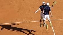 Mike, left, and Bob Bryan reacts after defeating doubles Max Mirnyi of Bulgaria and Daniel Nestor of Canada in their final match of the Monte Carlo Tennis Masters tournament in Monaco, Sunday. (Lionel Cironneau)