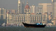 A fishing boat passes the Taj Mahal Hotel in Mumbai. (© Jayanta Shaw / Reuters/JAYANTA SHAW/REUTERS)
