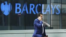 A city worker passes a Barclays bank branch in Canary Wharf, east London in this file photo. (© Olivia Harris/Reuters)