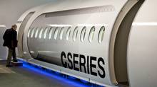 A reporter enters a full-size model of the Bombardier CSeries aircraft as it is introduced Monday, September 14, 2009 in Montreal. Qatar Airways, a potential key customer, has delayed talks with Bombardier about an order of the jets for the time being. (Paul Chiasson/The Canadian Press)