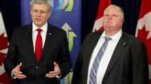 Prime Minister Stephen Harper speaks as Toronto Mayor Rob Ford, right, looks on, after announcing funding for new subways in Toronto on Sept. 22, 2013. (Mark Blinch/The Canadian Press)