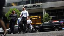 People walk outside a BlackRock Inc. building in New York in this file photo. Money held in all ETF products globally surpassed the $2-trillion (U.S.) mark last month, but almost 70 per cent of those assets are run by only three companies. (ERIC THAYER/REUTERS)