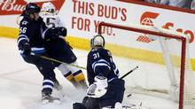 Winnipeg Jets' Marko Dano (56) is unable to stop Nashville Predators' Craig Smith (15) from scoring on goaltender Ondrej Pavelec (31) during third period NHL hockey action in Winnipeg on Tuesday, March 8, 2016. (Trevor Hagan/THE CANADIAN PRESS)
