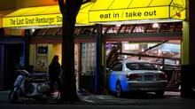 A police officer, left, walks past the scene as an employee of a Fatburger restaurant looks on after a car crashed into the restaurant injuring four on duty police officers that were having dinner in Vancouver late Sunday November 3, 2013. (DARRYL DYCK/THE CANADIAN PRESS)