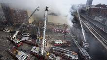 Firefighters battle a fire after a building collapse in the East Harlem neighborhood of New York, Wednesday, March 12, 2014 (John Minchillo/AP)