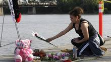 A woman places flowers at a vigil for 15 year old Tina Fontaine on the Alexander Docks along the Red river from which her body, in a bag, was recovered Sunday in Winnipeg Manitoba, August 19, 2014. (LYLE STAFFORD For The Globe and Mail)