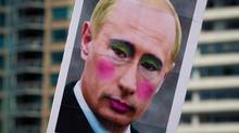 A poster of Russian President Vladimir Putin sporting makeup is carried during the Vancouver Pride Parade in Vancouver, on Sunday August 4, 2013. (DARRYL DYCK/THE CANADIAN PRESS)
