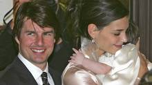 Actors Tom Cruise and Katie Holmes leave a restaurant with their daughter Suri in Rome November 16, 2006. (MAX ROSSI/REUTERS)