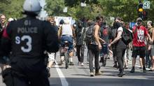 Protesters flee from in front of the Hydro Quebec building as riot police move in and clear the area during an anti-government protest in Montreal, Quebec on Wednesday, August 8, 2012. (Peter McCabe/THE CANADIAN PRESS)