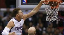 Los Angeles Clippers Blake Griffin (L) slam dunks over Dallas Mavericks Chris Kaman during their NBA game in Los Angeles, California, December 5, 2012. (LUCY NICHOLSON/REUTERS)