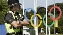 A British policeman stand guards in front the Olympic rings logo, in Coventry, England, Tuesday, July 24, 2012. Opening ceremonies for the 2012 London Olympics will be held Friday, July 27. (Hussein Malla/The Associated Press)