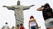 Tourists take picture in front of Brazil's most famous landmark, Christ, the Redeemer statue, (VANDERLEI ALMEIDA/VANDERLEI ALMEIDA/AFP/GETTY IMAGES)