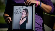 Carol Todd holds a photograph of her late daughter Amanda Todd signed by U.S. singer Demi Lovato with the words 'Stay Strong.' (DARRYL DYCK/THE CANADIAN PRESS)