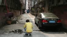 A Dongguan resident squats in a squalid alley in Dongguan, China. The city's high crime rate and emptying factories spur comparisons to Flint, Michigan. (Yu Mei for The Globe and Mail)