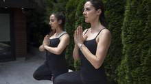 TORONTO, ONTARIO: July 12, 2013 - Grace Fusillo-Lombardi (right), 40, and her daughter Allessandra, 16, wear Lululemon pants while practicing yoga poses at their home in Toronto, Ontario. (Philip Cheung For The Globe and Mail)