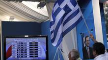 New Democracy party supporters wave a Greek flag as a TV screen shows resultsin Athens on June 17, 2012. (Petros Giannakouris/AP)