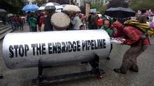 Protestors load a giant piece of pipeline with their placards following a protest outside the Vancouver Art Gallery in downtown Vancouver, Tuesday, August 31, 2010. The pipeline was brought there by opponents of the Northern Gateway Pipeline Project which would see a gas pipeline built in northern B.C. (THE CANADIAN PRESS/Jonathan Hayward/THE CANADIAN PRESS/Jonathan Hayward)