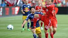 TFC's Jeremy Brockie (right) fights for the ball against New York Red Bulls' Kosuke Kimur during the fist half of their MLS soccer game Saturday July 20, 2013 in Toronto. (Jon Blacker/THE CANADIAN PRESS)