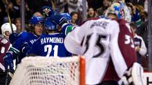 Vancouver Canucks' David Booth, from left, Mason Raymond and Ryan Kesler celebrate booth's goal as Colorado Avalanche goalie Jean-Sebastien Giguere looks on during the first period of an NHL hockey game in Vancouver, B.C., on Wednesday February 15, 2012. (DARRYL DYCK/THE CANADIAN PRESS)
