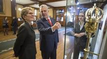 Ontario Premier Kathleen Wynne and her Quebec counterpart, Philippe Couillard, discuss the ceremonial mace on display at the Ontario Legislature in Toronto during a break from Friday meetings. (Chris Young/THE CANADIAN PRESS)