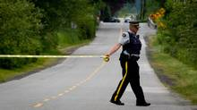 An RCMP oficer puts up police tape down the road from where murder suspect Angus David Mitchell was shot by officers in rural Maple Ridge, B.C., before dying in hospital on May 30. (Darryl Dyck for The Globe and Mail)