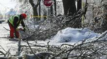 Workers clear debris in Brampton, Ont., after the Christmas-week ice storm that knocked out power to hundreds of thousands of homes in Ontario. (KEVIN VAN PAASSEN/THE GLOBE AND MAIL)