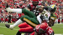 Edmonton Eskimos' Jerome Messam, centre, tries to get past Calgary Stampeders' Demonte Bolden, left, and Keon Raymond during first half CFL football action in Calgary, Alta., Monday, Sept. 3, 2012. (The Canadian Press)