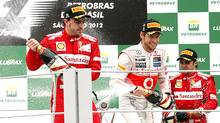 (L to R) Second placed Ferrari Formula One driver Fernando Alonso of Spain, race winner McLaren's Jenson Button of Britain and third placed driver Felipe Massa of Brazil celebrate on the podium after the Brazilian F1 Grand Prix at Interlagos circuit in Sao Paulo November 25, 2012. (PAULO WHITAKER/REUTERS)