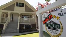 A sold sign is pictured outside a home in Vancouver on June, 28, 2016. (JONATHAN HAYWARD/THE CANADIAN PRESS)
