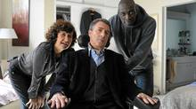 In this film image released by The Weinstein Company, Anne Le, left, Francois Cluzet, and Omar Sy, right, are shown in a scene from 'The Intouchables.' (Thierry Valletoux / AP)