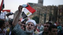An Egyptian man holds the Quran as he celebrates Islamist candidate Mohammed Morsi's apparent victory in Tahrir Square, Cairo, Monday, June 18, 2012. (Manu Brabo/AP)
