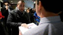 Jorge Salazar, centre left, presents a petition seeking an inquiry into the death of Lucia Vega Jiminez to a Canadian Border Services Agency official at the CBSA office in Vancouver on Feb. 5, 2014. (Darryl Dyck for The Globe and Mail)