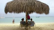 Tourists relax on Palm Beach in Aruba. (LESLIE MAZOCH/AP)