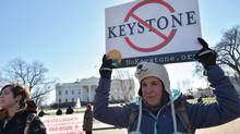 A woman holds a placard during a protest outside of the White House against the building of the proposed Keystone XL oil pipeline on January 10, 2015 in Washington, DC. (MANDEL NGAN/AFP/Getty Images)