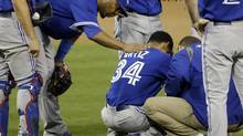 Toronto Blue Jays third baseman Edwin Encarnacion, left, tries to console starting pitcher Ramon Ortiz (34) after Ortiz injured himself while pitching against the San Diego Padres during the third inning in an interleague baseball game Sunday, June 2, 2013, in San Diego. (Gregory Bull/AP)