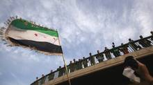A demonstrator waves a Syrian flag during a protest against Syria's President Bashar al-Assad, upon the meeting of the Arab Foreign ministers in Cairo February 12, 2012. (MOHAMMED SALEM/REUTERS/MOHAMMED SALEM/REUTERS)