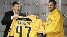 Nashville Predators forward Alexander Radulov, right, of Russia, poses with general manager David Poile, left, at a news conference on Wednesday. (Mark Humphrey/Associated Press)