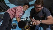 Jeongwan Jin and Chris Pugh of the University of Waterloo's Institute for Quantum Computing install a telescope in a National Research Council operated aircraft. The telescope was used to detect a laser beam transmitted from the ground that carries a coded message. Researchers hope to the deploy the technology on a future satellite that would be capable of sending secure information across the globe. (National Research Council)