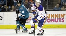 Connor McDavid of the Oilers skates past Logan Couture of the Sharks during Game 3 in San Jose on Sunday night. (Marcio Jose Sanchez/AP)