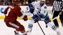 Vancouver Canucks' Jason Garrison (5) passes the puck in front of Phoenix Coyotes' Matthew Lombardi, left, during the first period in an NHL game on Thursday, March 21, 2013, in Glendale, Ariz. (Ross D. Franklin/AP)