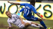 Vancouver Whitecaps' Jay DeMerit, left, tackles Montreal Impact's Sanna Nyassi during the first half of an MLS soccer game in Vancouver, B.C., on Saturday March 10, 2012. THE CANADIAN PRESS/Darryl Dyck (Darryl Dyck/CP)