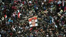 Egyptians hold a picture of a man killed during the uprising that ousted president Hosni Mubarak at Cairo's Tahrir Square on Feb. 18, 2011 during celebrations marking one week after Mubarak was forced out of office by an unprecedented wave of protests in the Arab world's most populous country. (PEDRO UGARTE/AFP/Getty Images/PEDRO UGARTE/AFP/Getty Images)