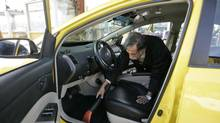 A driver vacuums his taxi cab. (Laura Leyshon for The Globe and Mail)