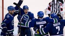 Vancouver Canucks defenceman Jason Garrison (5) celebrates his game winning goal with teammates Dan Hamhuis (2), Mike Santorelli (25) and David Booth (7) during the overtiime period of NHL action at Rogers Arena in Vancouver, B.C. Tuesday, Oct. 8, 2013. (The Canadian Press)