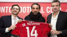 Tim Bezbatchenko, Toronto FC general manager, Dwayne De Rosario, centre, and Ryan Nelsen, Toronto FC head coach poses for a photographer after the Toronto FC of the MLS soccer league signed De Rosario to a new deal with his former club in Toronto on Thursday, January 9, 2014. (The Canadian Press)