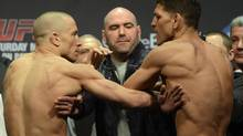 Fighters Georges St-Pierre and Nick Diaz are separated during the weight-in for UFC 158 in Montreal on Friday March 15, 2013. (Ryan Remiorz/THE CANADIAN PRESS)